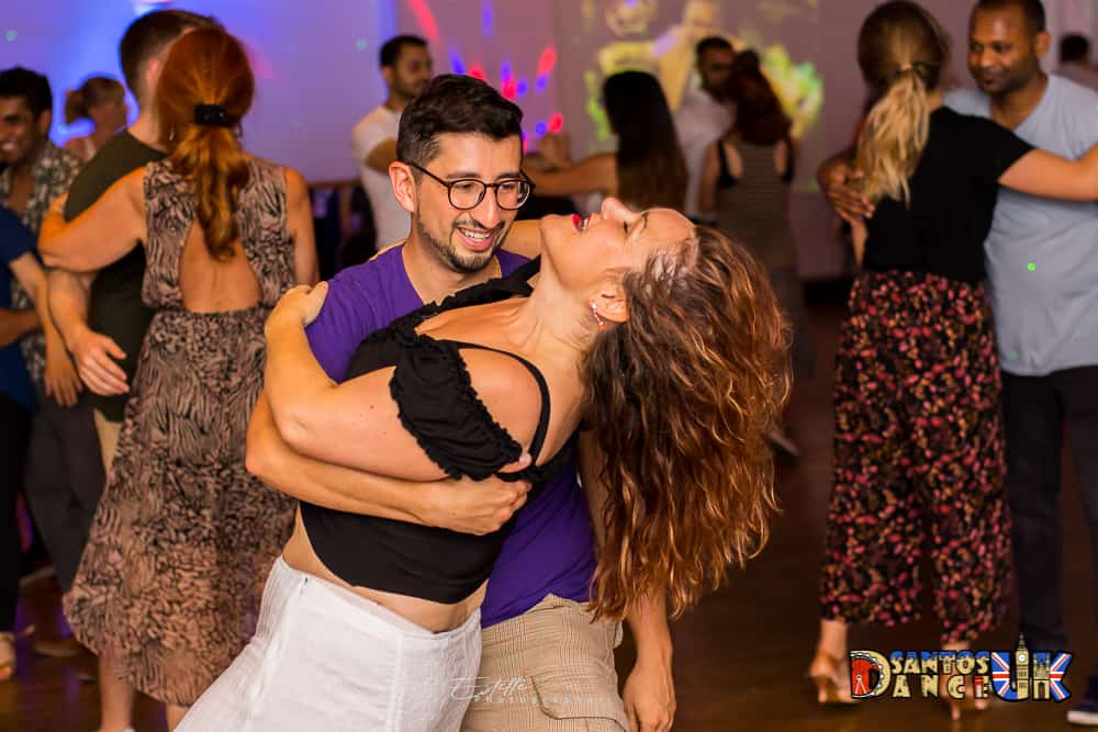 Dancing bachata woman leans back when man is holding her