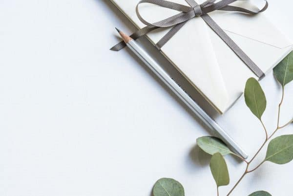 Envelopes on the table wrapped with a silver ribbon next to the pencil