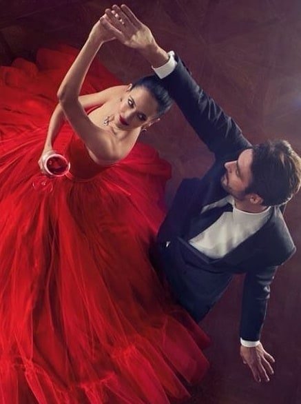 Women in a red dress dancing with a man wearing suit and tie